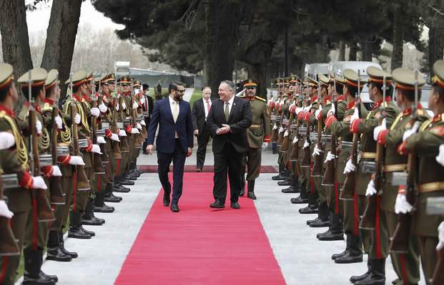 U.S. Secretary of State Mike Pompeo, center right, and Afghan National Security Adviser Hamdullah Mohib, center left, review an honor guard, during an arrival ceremony at the Presidential Palace in Kabul, Afghanistan, Monday, March 23, 2020. Pompeo was in Kabul on an urgent visit Monday to try to move forward a U.S. peace deal signed last month with the Taliban, a trip that comes despite the coronavirus pandemic, at a time when world leaders and statesmen are curtailing official travel. (Afghan Presidential Palace via AP)