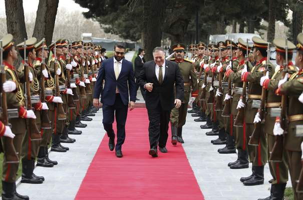 U.S. Secretary of State Mike Pompeo, right, and Afghanistan's National Security Adviser Hamdullah Mohib, arrives at the Presidential Palace in Kabul, Afghanistan, Monday, March 23, 2020. Pompeo was in Kabul on an urgent visit Monday to try to move forward a U.S. peace deal signed last month with the Taliban, a trip that comes despite the coronavirus pandemic, at a time when world leaders and statesmen are curtailing official travel. (Afghan Presidential Palace via AP)