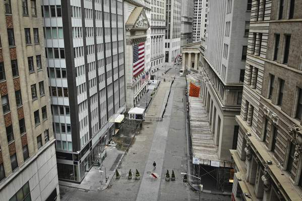 "FILE - In this Saturday, March 21, 2020 file photo, a lone pedestrian wearing a protective mask walks past the New York Stock Exchange as coronavirus concerns empty a typically bustling downtown area in New York. Stocks around the world swung lower Monday, March 23 even after the Federal Reserve announced a tidal wave of support for lending markets, going way beyond the ""bazooka"" it had already unloaded. (AP Photo/John Minchillo, File)"