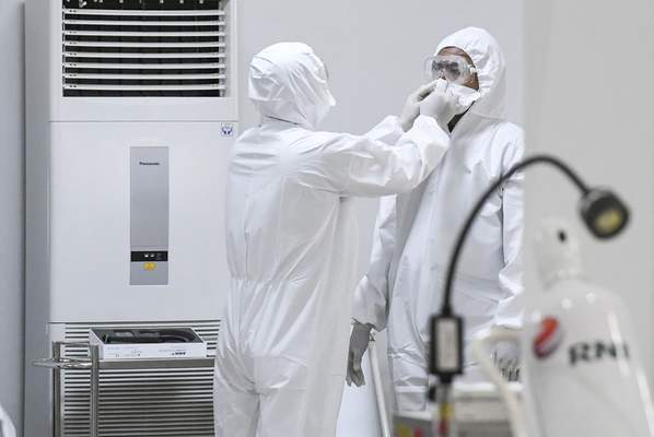 A staff member assists a colleague to don his protective gears at an emergency hospital set up amid the new coronavirus outbreak in Jakarta, Indonesia, Monday, March 23, 2020. (Hafidz Mubarak A/Pool Photo via AP)