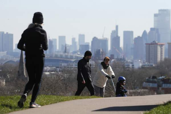 Pedestrians walk on Primrose Hill with the skyline of central London as a backdrop in London, Monday, March 23, 2020. (AP Photo/Frank Augstein)
