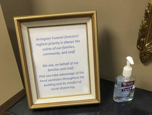 This March 19, 2020, photo provided by Bob Arrington of Arrington Funeral Directors shows a sign requesting visitors to use hand sanitizer and maintain social distancing amid the coronavirus outbreak, at their funeral home in Jackson, Tenn. (Cliff Walker Jr./Arrington Funeral Directors via AP)