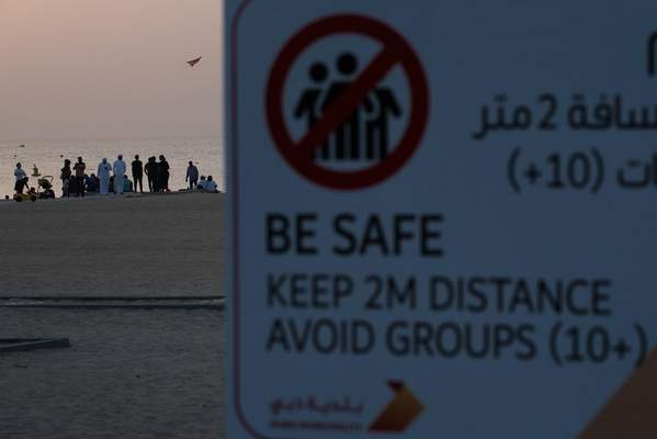 A crowd of more than 10 people gather on a beach despite a sign warning passers-by to maintain a distance from each other over the outbreak of the new coronavirus in Dubai, United Arab Emirates, Friday, March 20, 2020. (AP Photo/Jon Gambrell)