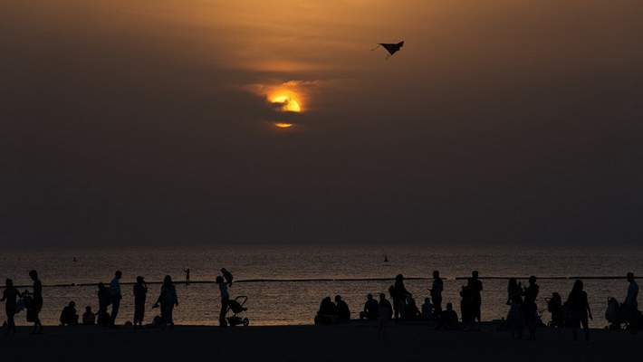 A crowd of more than 10 people gather on a beach despite warnings to maintain a distance from each other over the outbreak of the new coronavirus in Dubai, United Arab Emirates, Friday, March 20, 2020. (AP Photo/Jon Gambrell)