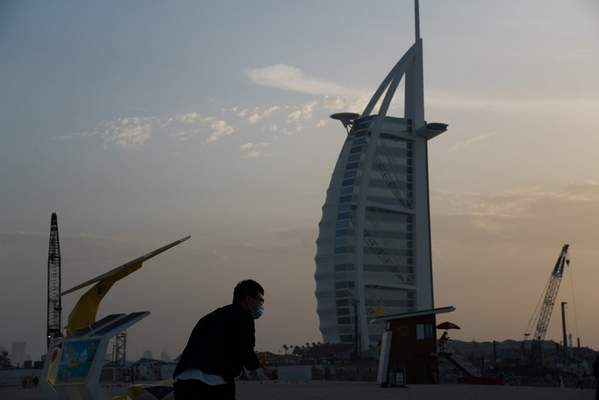 A tourist wearing a surgical mask bends down to take a picture in front of the sail-shaped Burj Al Arab luxury hotel in Dubai, United Arab Emirates, Friday, March 20, 2020. (AP Photo/Jon Gambrell)