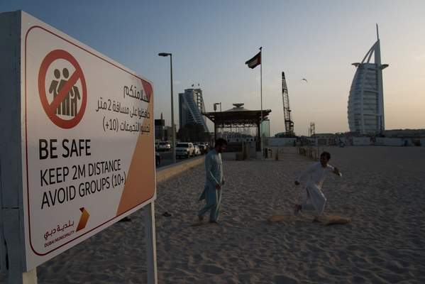Two laborers play tag near a sign warning people to maintain a distance from each other over the outbreak of the new coronavirus in front of the sail-shaped Burj Al Arab luxury hotel in Dubai, United Arab Emirates, Friday, March 20, 2020. (AP Photo/Jon Gambrell)