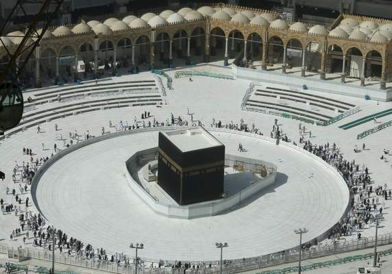 Muslims circumambulate the Kaaba, the cubic building at the Grand Mosque, in the Muslim holy city of Mecca, Saudi Arabia, Saturday, March 7, 2020. (AP Photo/Amr Nabil)