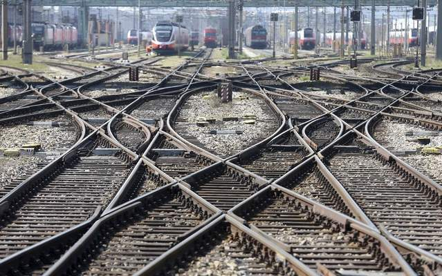 Railway trains stand in front of a train station in Vienna, Austria, Tuesday, March 24, 2020. (AP Photo/Ronald Zak)