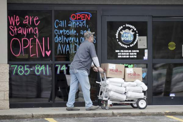 A pet store receives a delivery In Lawrence, Kan., Tuesday, March 24, 2020. The store offers curbside and delivery options to their customers. (AP Photo/Orlin Wagner)