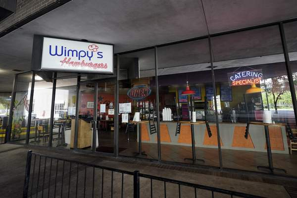 Chairs sit on top of tables inside a closed Wimpy's Hamburgers in downtown Houston, Tuesday, March 24, 2020. (AP Photo/David J. Phillip)