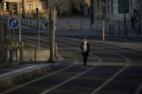 A woman walks on empty tram rails in Lyon, central France, Monday, March 23, 2020. (AP Photo/Laurent Cipriani)