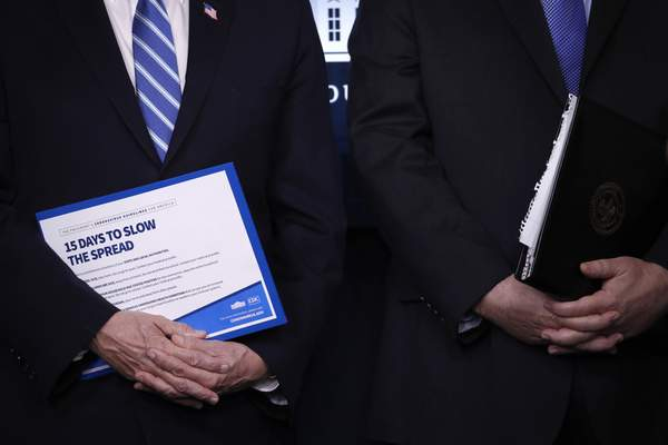 Vice President Mike Pence, left, and Attorney General William Barr hold binders as President Donald Trump speaks about the coronavirus in the James Brady Briefing Room, Monday, March 23, 2020, in Washington. (AP Photo/Alex Brandon)