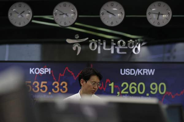 A currency trader walks by screens showing the Korea Composite Stock Price Index (KOSPI), left, and the foreign exchange rate between U.S. dollar and South Korean won at the foreign exchange dealing room in Seoul, South Korea, Tuesday, March 24, 2020. (AP Photo/Lee Jin-man)