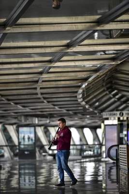 Benat Erro Diez, a young student musician plays his clarinet in the empty Loiu airport, near to Bilbao, northern Spain, Monday, March 23, 2020. (AP Photo/Alvaro Barrientos)