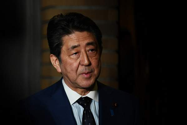 Japan's Prime Minister Shinzo Abe talks to journalists in front of the prime minister's residence in Tokyo, Tuesday, March 24, 2020. Abe says IOC president has agreed