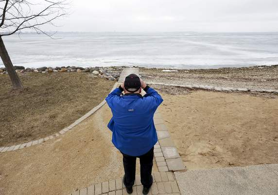 Associated Press Ed Hopkins, assistant climatologist with the Wisconsin State Climatology Office, uses binoculars to survey the surface of Lake Mendota in Maple Bluff, Wis.