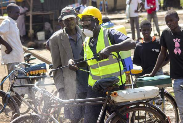 A man sprays disinfectant on a bicycle taxi in the Kibuye Market area of Kisumu in western Kenya Wednesday, March 25, 2020. (AP Photo/Amos Aura)