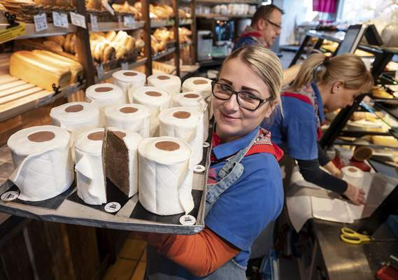 A saleswoman of the bakery Schuerener Backparadies shows a tray with round marble cakes wrapped in fondant that look like toilet paper rolls in Dortmund, Germany, Wednesday, March 25, 2020. The toilet paper cake has become a