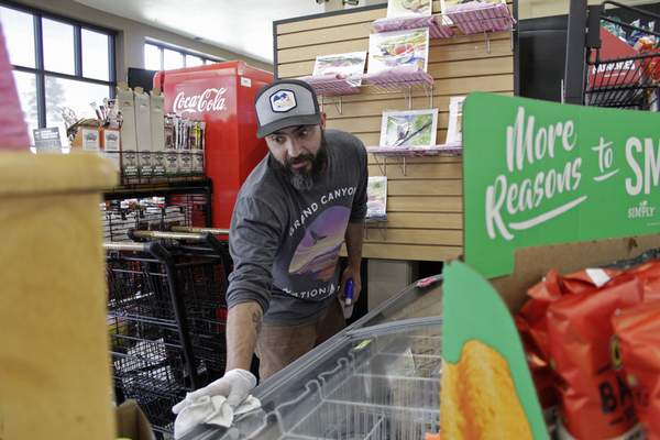 In this photo taken March 20, 2020, Mike Johnston, a clerk at the Maupin Market in tiny Maupin, Oregon, wipes down the ice cream case to protect customers from the new coronavirus. Tiny towns tucked into Oregon's windswept plains and cattle ranches miles from anywhere in South Dakota might not have had a single case of the new coronavirus yet, but their residents fear the spread of the disease to areas with scarce medical resources, the social isolation that comes when the only diner in town closes its doors and the economic free fall that's already hitting them hard. (AP Photo/Gillian Flaccus)
