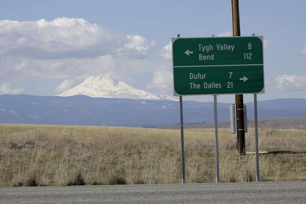 In this photo taken March 20, 2020, a sign indicates the distance to the nearest towns as cloud-capped Mount Hood rises in the background in this photo taken near Dufur, Oregon. Tiny towns tucked into Oregon's windswept plains and cattle ranches miles from anywhere in South Dakota might not have had a single case of the new coronavirus yet, but their residents fear the spread of the disease to areas with scarce medical resources, the social isolation that comes when the only diner in town closes its doors and the economic free fall that's already hitting them hard. (AP Photo/Gillian Flaccus)