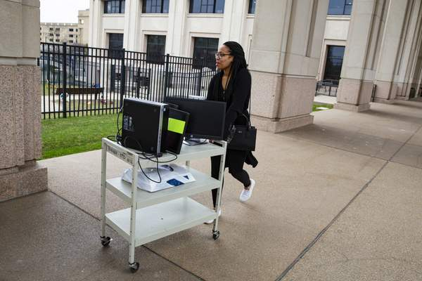 An employee at the Indiana Department of Revenue moves her computer equipment from her office at the State office complex in Indianapolis, Tuesday, March 24, 2020, to allow her to work from home. Indiana Gov. Eric Holcomb ordered state residents to remain in their homes except when they are at work or for permitted activities, such as taking care of others, obtaining necessary supplies, and for health and safety. The order is in effect from March 25 to April 7. (AP Photo/Michael Conroy)