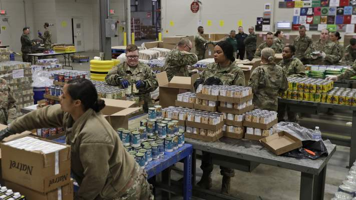"""Members of The Ohio National Guard assist in repackaging emergency food boxes for food distribution at the Cleveland Food Bank, Tuesday, March 24, 2020, in Cleveland. State parks have shuttered cabins, golf courses and marinas as Ohio enters its first full day of a statewide """"stay at home"""" order to slow the spread of the coronavirus. Grocery stores, gas stations and other essential businesses remain open. (AP Photo/Tony Dejak)"""