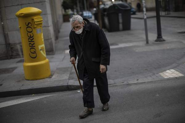An elderly men wears a safety mask during the coronavirus outbreak in Madrid, Spain, Tuesday, March 24, 2020. (AP Photo/Bernat Armangue)