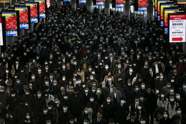 FILE - In this Tuesday, March 3, 2020, file photo, a large crowd wearing masks commutes through Shinagawa Station in Tokyo. (AP Photo/Jae C. Hong, File)
