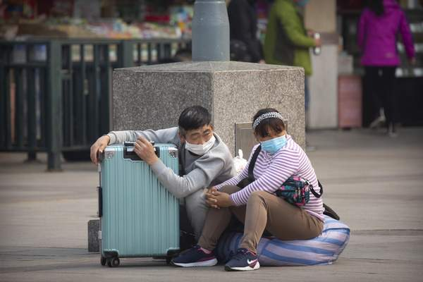 Travelers wearing face masks sit with their luggage outside the Beijing Railway Station in Beijing, Wednesday, March 25, 2020. (AP Photo/Mark Schiefelbein)
