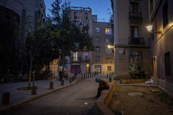 In this Friday, March 20, 2020 photo, Gana Gutierrez sits in an empty street in Barcelona, Spain. (AP Photo/Emilio Morenatti)