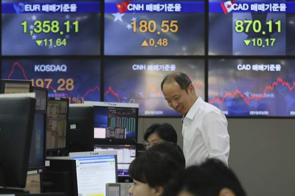 A currency trader smiles at the foreign exchange dealing room of the KEB Hana Bank headquarters in Seoul, South Korea, Wednesday, March 25, 2020. (AP Photo/Ahn Young-joon)