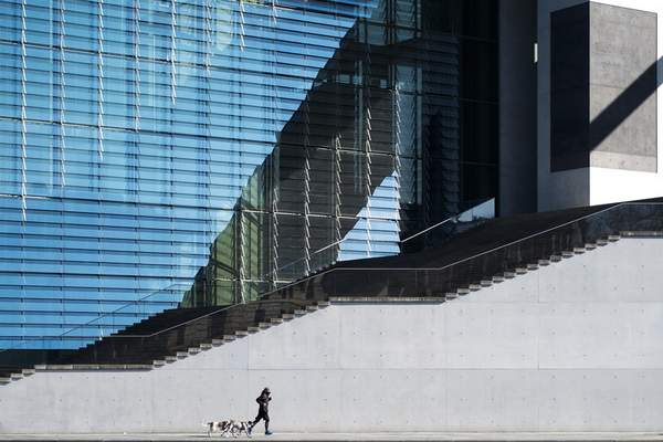 A lonely man runs with two dogs in front of a parliament building in the government district in Berlin, Germany, Wednesday, March 25, 2020. (AP Photo/Markus Schreiber)