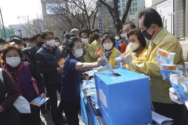 A woman puts an envelope containing a face mask into a charity box as South Korean Prime Minister Chung Se-kyun, right, watches during a campaign for the donation of face masks to impoverished people amid the spread of the new coronavirus in Seoul, South Korea, Wednesday, March 25, 2020. (AP Photo/Ahn Young-joon)