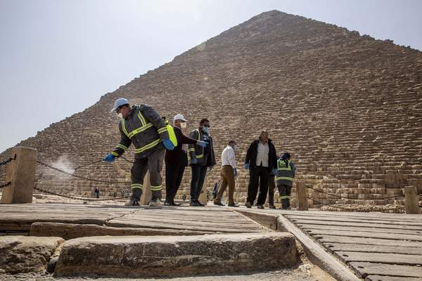 Municipal workers sanitize the walkways around the Giza pyramid complex in hopes of curbing the spread of the new coronavirus outbreak in Egypt, Wednesday, March 25, 2020. (AP Photo/Nariman El-Mofty)
