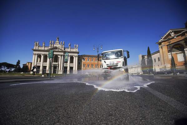 A truck sprays disinfectant as a preventive measure against the spread of the new coronavirus, in Rome, Wednesday, March 25, 2020. (AP Photo/Andrew Medichini)