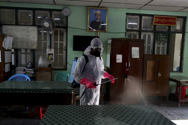 A member of the Yangon City and Development Committee disinfects government offices to help curb the spread of the new coronavirus in Yangon, Myanmar Wednesday, March 25, 2020. (AP Photo/Thein Zaw)