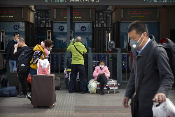 Travelers wearing face masks walk outside the Beijing Railway Station in Beijing, Wednesday, March 25, 2020. (AP Photo/Mark Schiefelbein)