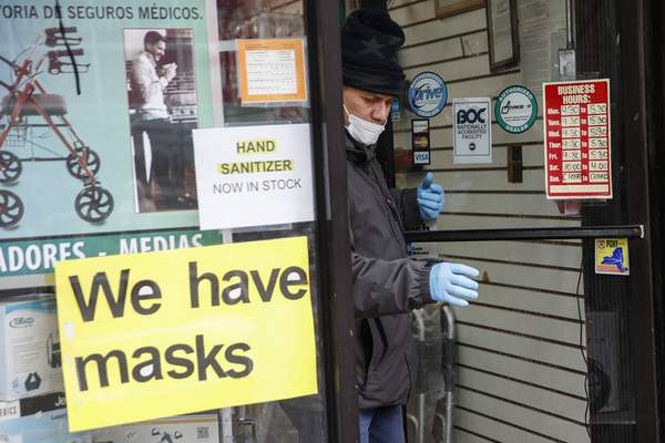 Associated Press A customer leaves a shop advertising personal protective equipment Wednesday near Elmhurst Hospital Center in New York.