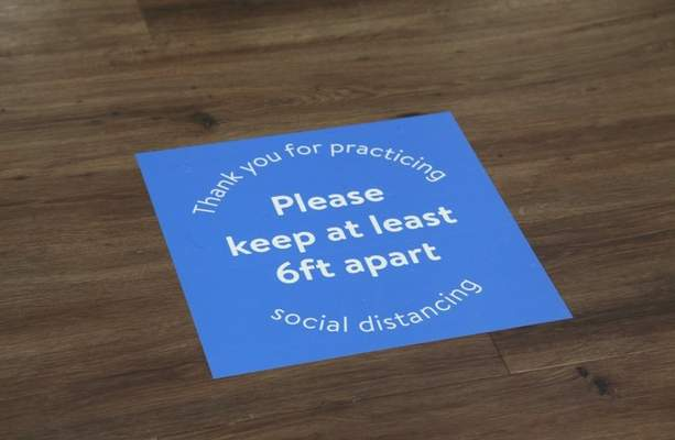 Walmart, along with Kroger and Meijer, have placed floor decals around its stores reminding customers of social distancing.