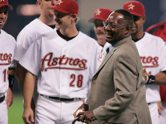 "FILE - In this June 25, 2005, file photo, former Houston Astro Jimmy Wynn is joined by current players as he prepares to throw out the ceremonial first pitch after his jersey number was retired in Houston. Wynn, the slugger who earned his nickname of ""The Toy Cannon"" during his days with the Astros in the 1960s and '70s, has died. Wynn was 78. The Astros said he died Thursday, March 26, 2020, in Houston, but did not provide further details. (AP Photo/Pat Sullivan, File)"