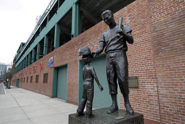 A statue of former Boston Red Sox baseball player Ted Williams, right, stands outside Fenway Park, March 25, 2020, in Boston. (AP Photo/Steven Senne)