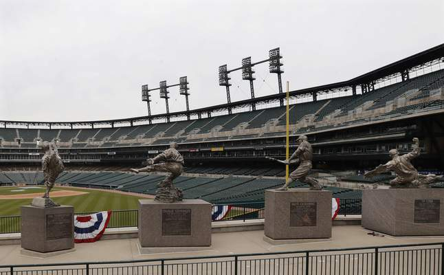 The statues of, from left, Hal Newhouser, Charlie Gehringer, Hank Greenberg and Ty Cobb stand in left field inside Comerica Park, home of the Detroit Tigers baseball team, March 26, 2020, in Detroit. (AP Photo/Carlos Osorio)