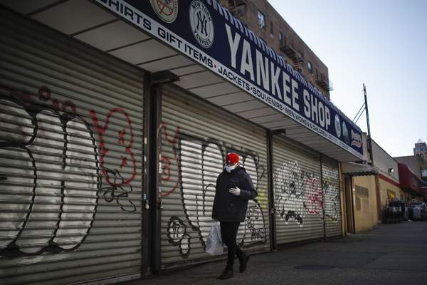 A pedestrian passes by a New York Yankees baseball souvenir shop, March 26, 2020, in the Bronx borough of New York. To baseball fans, opening day is an annual rite of spring that evokes great anticipation and warm memories. This year's season was scheduled to begin Thursday, but there will be no games for a while because of the coronavirus outbreak. (AP Photo/John Minchillo)