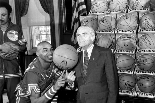 FILE - In this Feb. 15, 1977, file photo, the Harlem Globetrotters' Fred Curly Neal of shows New York City Mayor Abe Beame the art of balancing a basketball on a finger during ceremony at City Hall. Neal, the dribbling wizard who entertained millions with the Harlem Globetrotters for parts of three decades, has died the Globetrotters announced Thursday, March 26, 2020. He was 77. Neal played for the Globetrotters from 1963-85, appearing in more than 6,000 games in 97 countries for the exhibition team known for its combination of comedy and athleticism. (AP Photo/File)