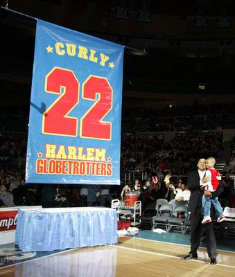 FILE - In this Feb. 15, 2008, file photo, Harlem Globetrotters' Fred Curly Neal looks on with his grandson Jaden Neal-Roberts as his No. 22 is retired by the world renowned Harlem Globetrotters at Madison Square Garden in New York. Neal, the dribbling wizard who entertained millions with the Harlem Globetrotters for parts of three decades, has died the Globetrotters announced Thursday, March 26, 2020. He was 77. Neal played for the Globetrotters from 1963-85, appearing in more than 6,000 games in 97 countries for the exhibition team known for its combination of comedy and athleticism. (AP Photo/Frank Franklin II, File)