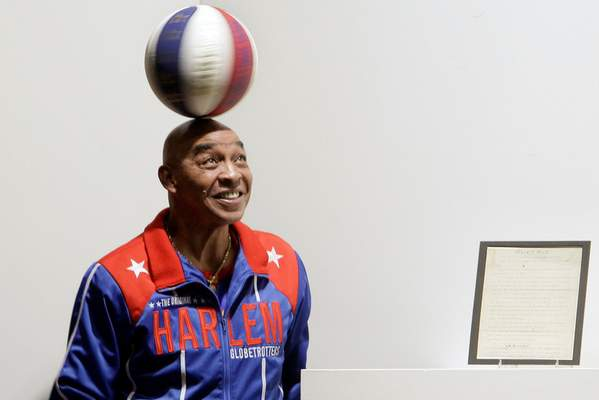FILE - In this Dec. 10, 2010, file photo, Harlem Globetrotters Fred Curly Neal spins a ball on his head prior to the bidding for the Naismith Rules, the original rules for basketball, framed at right, at Sotheby's in New York. Neal, the dribbling wizard who entertained millions with the Harlem Globetrotters for parts of three decades, has died the Globetrotters announced Thursday, March 26, 2020. He was 77. Neal played for the Globetrotters from 1963-85, appearing in more than 6,000 games in 97 countries for the exhibition team known for its combination of comedy and athleticism. (AP Photo/Richard Drew, File)
