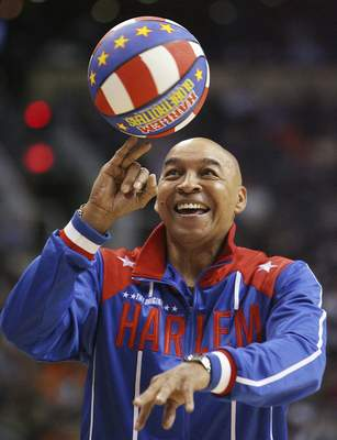 The Harlem Globetrotters' Fred Curly Neal performs during a timeout in the second quarter in an NBA basketball game between the Indiana Pacers and the Phoenix Suns in Phoenix. Neal, the dribbling wizard who entertained millions with the Harlem Globetrotters for parts of three decades, has died the Globetrotters announced Thursday, March 26, 2020. He was 77. Neal played for the Globetrotters from 1963-85, appearing in more than 6,000 games in 97 countries for the exhibition team known for its combination of comedy and athleticism. (AP Photo/Ross D. Franklin, File)