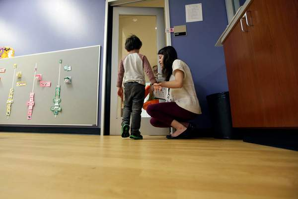 FILE - In this Monday, Oct. 24, 2016 file photo, Megan Krail helps a 4-year-old boy with Autism Spectrum Disorder practice trick-or-treating at The University of Texas at Dallas' Callier Center for Communication Disorders preschool class in Dallas. (AP Photo/LM Otero)