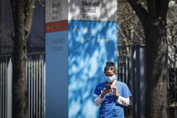 A medical worker uses her phone while wearing a surgical mask outside Mt. Sinai West, Thursday, March 26, 2020, in New York. (AP Photo/John Minchillo)
