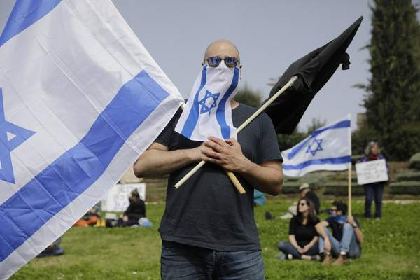 Israelis hold national flags during a protest against Prime Minister Benjamin Netanyahu outside the national parliament in Jerusalem, Monday, March 23, 2020. The opposition has accused Netanyahu of using the coronavirus crisis as cover to undermine the country's democratic institutions. With the country in near-shutdown mode, Netanyahu has already managed to postpone his own pending criminal trial and authorize unprecedented electronic surveillance of Israeli citizens. (AP Photo/Sebastian Scheiner)